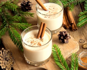Glasses of holiday egg nog surrounded by greenery and pinecones.