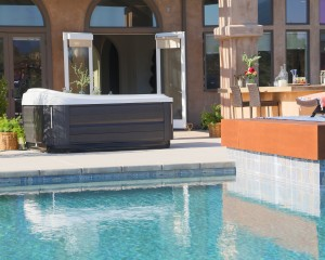 Outdoor Jacuzzi Hot Tub installation on a modern patio surrounded by an in-ground pool installation.